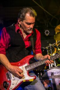 man in a red shirt playing a red guitar